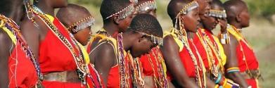 De kleurrijke kleding van de Masaï steken schril af tegen het vaak stoffige decor.